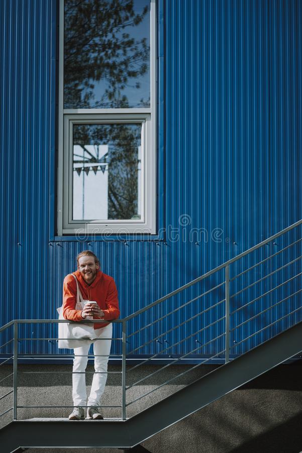 Happy hipster man with coffee on outdoor stairs. Urban lifestyle concept. Full length portrait of young happy red haired hipster man with cup of coffee staying royalty free stock photos