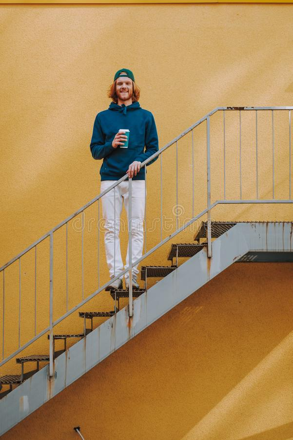 Happy hipster man with coffee on stairs. Urban lifestyle concept. Full length portrait of young red haired happy hipster guy staying on stairs outdoor with cup royalty free stock photography