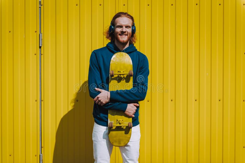 Happy hipster man with headphones and skateboard. Urban lifestyle and activity. Front view portrait of young smiling hipster guy with skateboard and headphones royalty free stock images