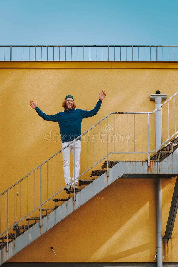 Happy hipster man holding hands up on stairs. Urban lifestyle concept. Full length portrait of young red haired happy hipster guy staying on stairs outdoor and stock photography