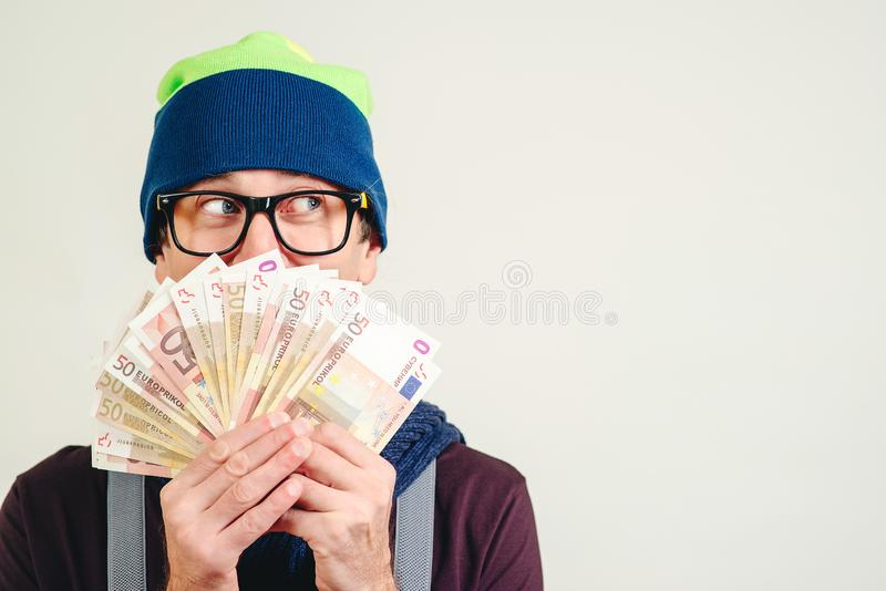 Happy hipster man holding money cash, on white background with copy space. Funny man in glasses holding euro bills, looking aside royalty free stock images