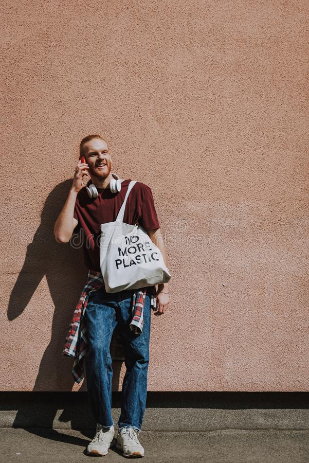 Happy hipster man talking by mobile phone. Urban lifestyle and safe environment. Full length portrait of young happy hipster guy with eco bag leaning on building stock photo