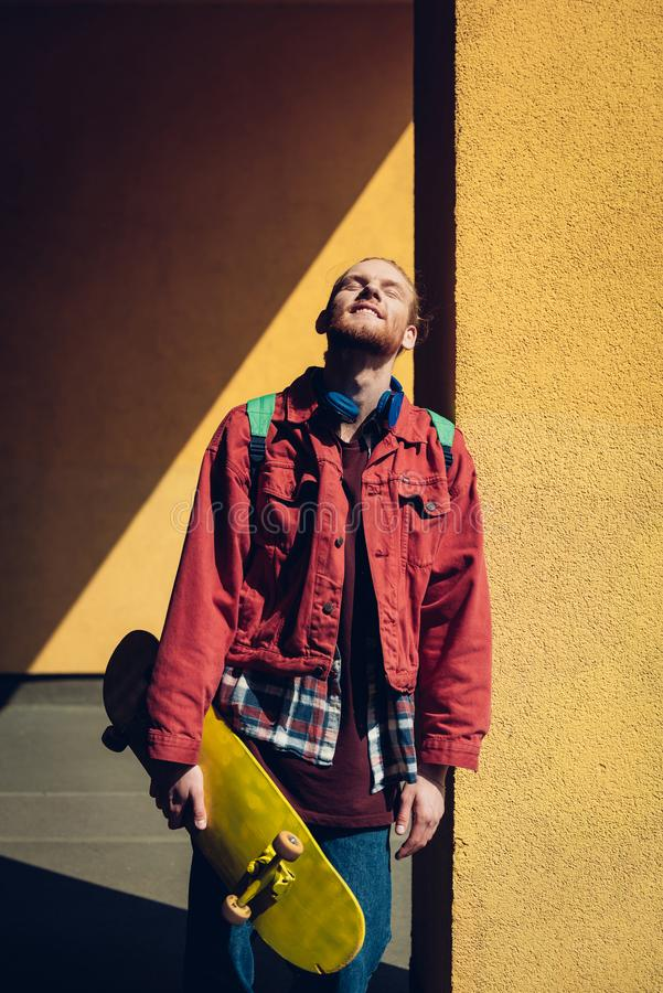 Happy hipster skater man enjoying sun light. Urban lifestyle and activity. Waist up portrait of happy young hipster guy with yellow skateboard leaning on royalty free stock photos