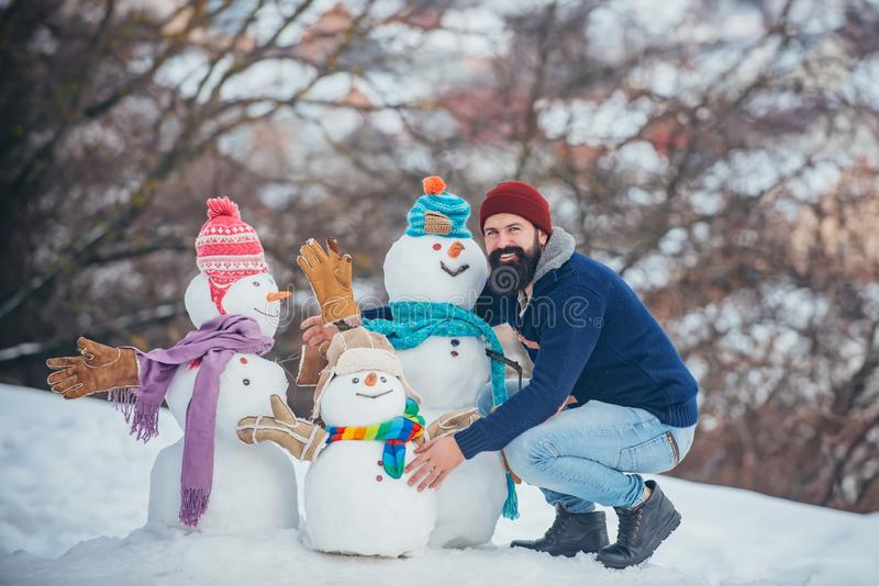 Happy hipster winter portrait. Handsome bearded man, father in winter clothes. Winter emotion. Funny snowmen. Happy. Father playing with a snowman on a snowy stock photos