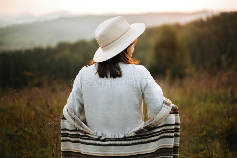 Happy hipster woman in poncho and hat enjoying traveling in evening mountains. Stylish boho girl walking in sunny light at. Atmospheric sunset in meadow. Space stock images