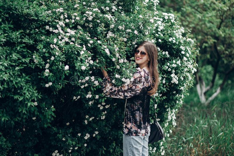 Happy hipster woman in sunglasses holding blooming bush with white flowers of spirea. boho girl smiling in floral clothes. space. For text. spring summer time stock photo
