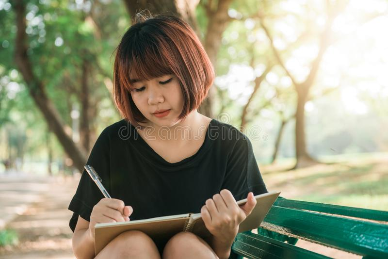 Happy hipster young asian woman writing into her diary in park. Happy hipster young asian woman working on notebook in park. stock image