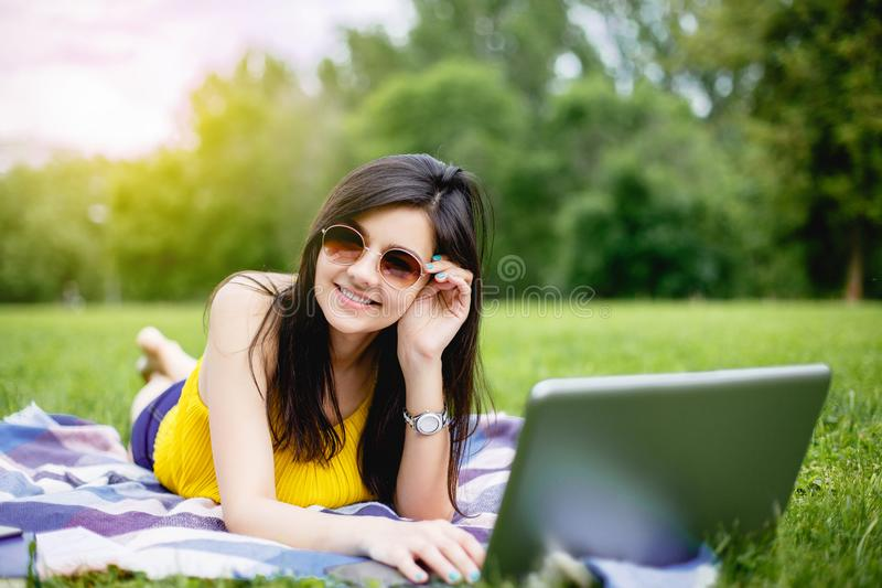 Happy hipster young woman working on laptop in the park. royalty free stock photo