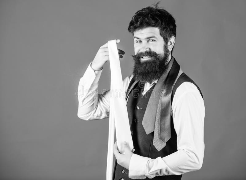Happy with his choice. Sales manager offering a good choice of design neckties. Brutal hipster making a choice. Bearded. Man choosing tie from luxury collection stock photos