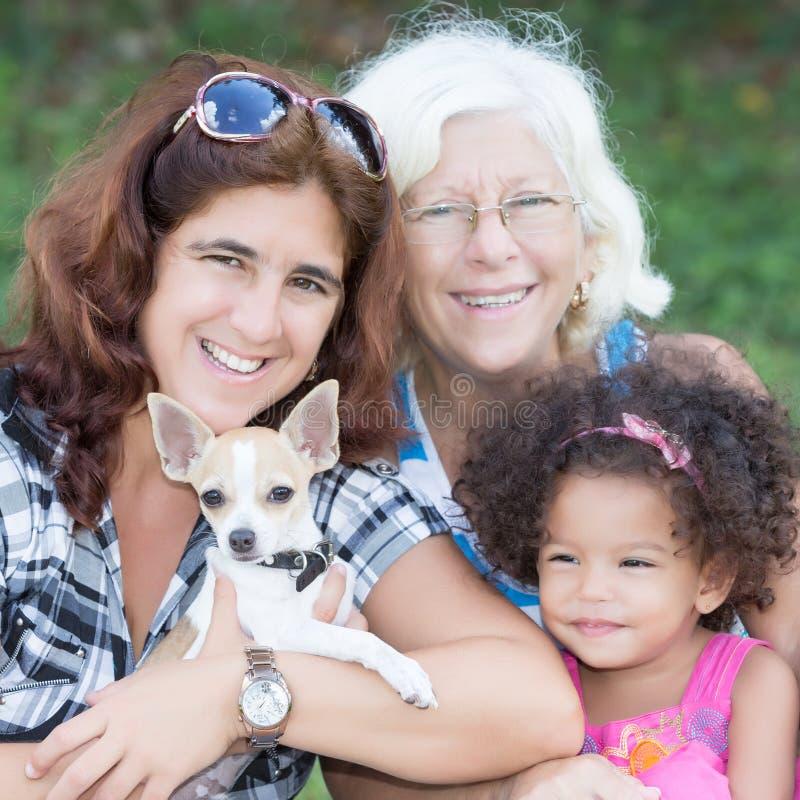 Happy hispanic family with a small dog stock photos
