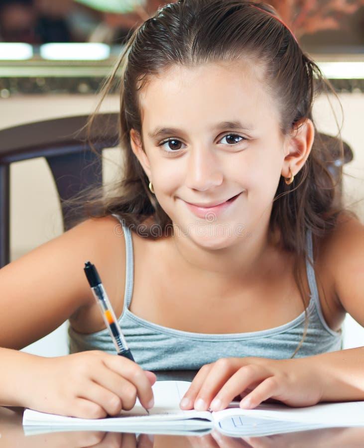 Happy hispanic girl working on her homework royalty free stock photo