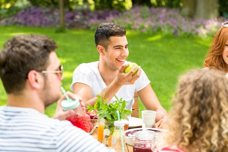 Happy hispanic man eating an apple during a meeting with his fri. Happy hispanic men eating an apple during a meeting with his friends on the patio stock images