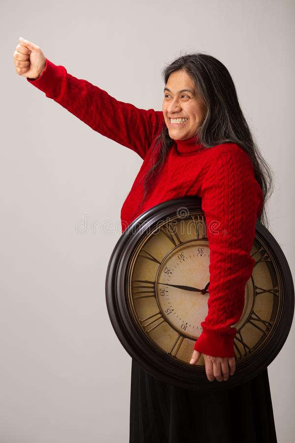 Happy Hispanic Woman With Clock Under Arm Lifts Fist Triumphantly royalty free stock images