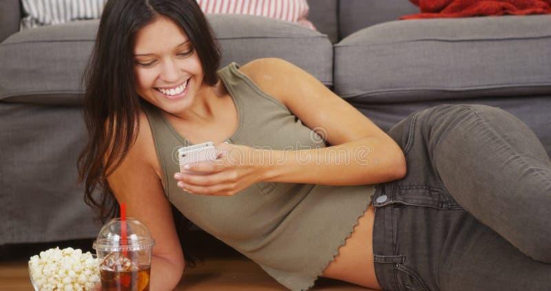 Happy hispanic woman lying on floor texting royalty free stock photo