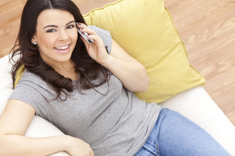 Happy Hispanic Woman Using Cell Phone At Home stock image