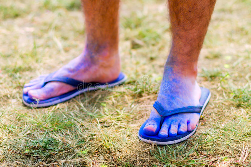 Happy Holi Fest. Body parts.Close-up shooting of guy`s feet wearing blue flip-flops stained with colorful powder royalty free stock photos