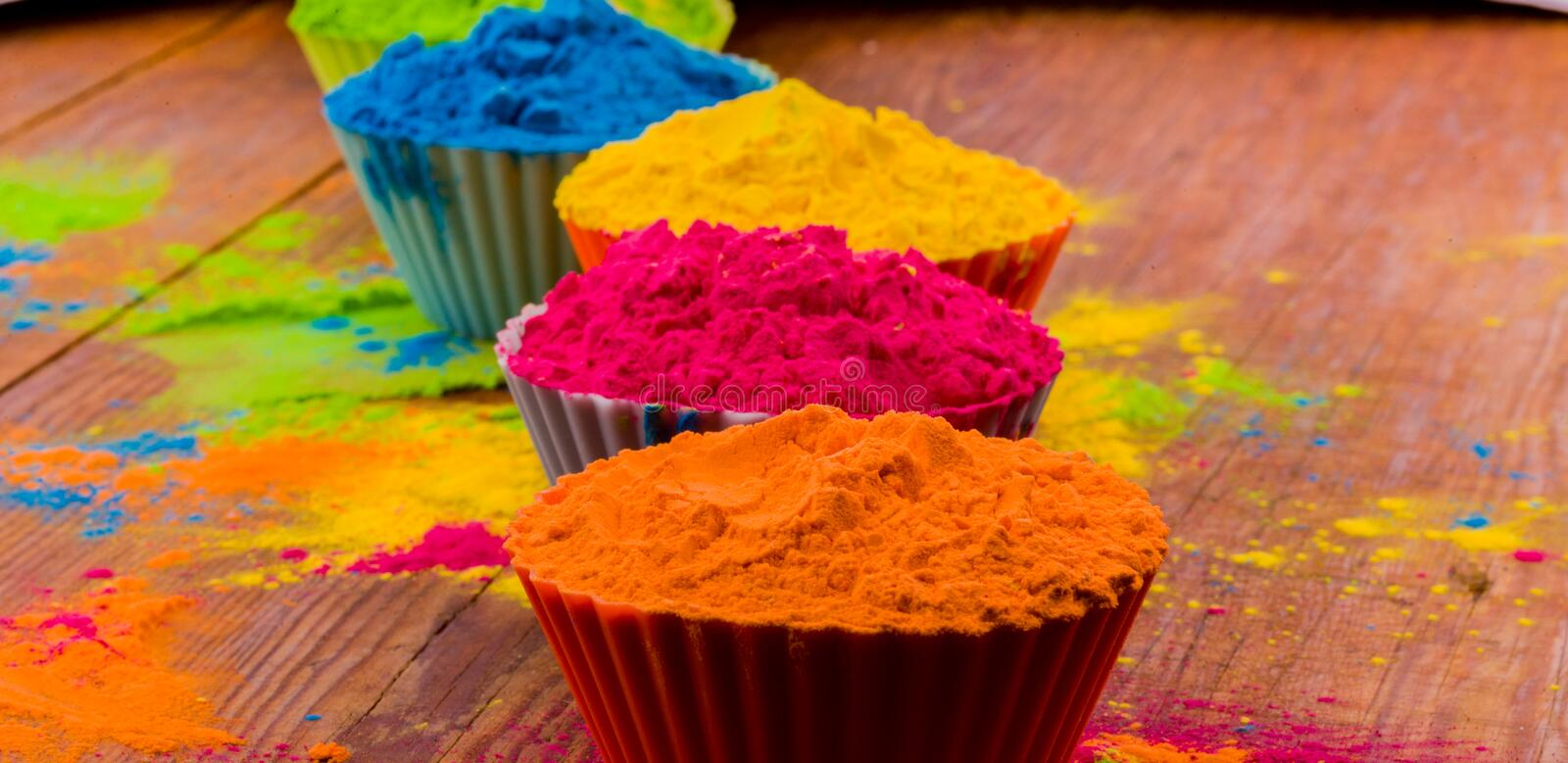 Happy Holi greeting card designed showing Indian traditional sweet and salty food, flowers and powder colours arranged over white royalty free stock photography