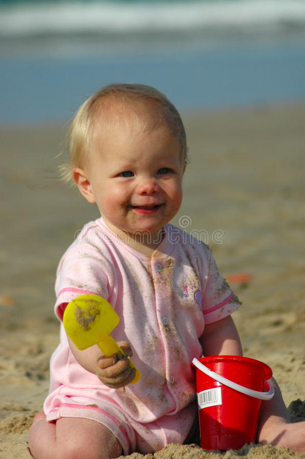 Happy holiday baby. A little Caucasian white blond baby with blue eyes and cute and happy expression in the face sitting in the sand and playing with her toys on stock image