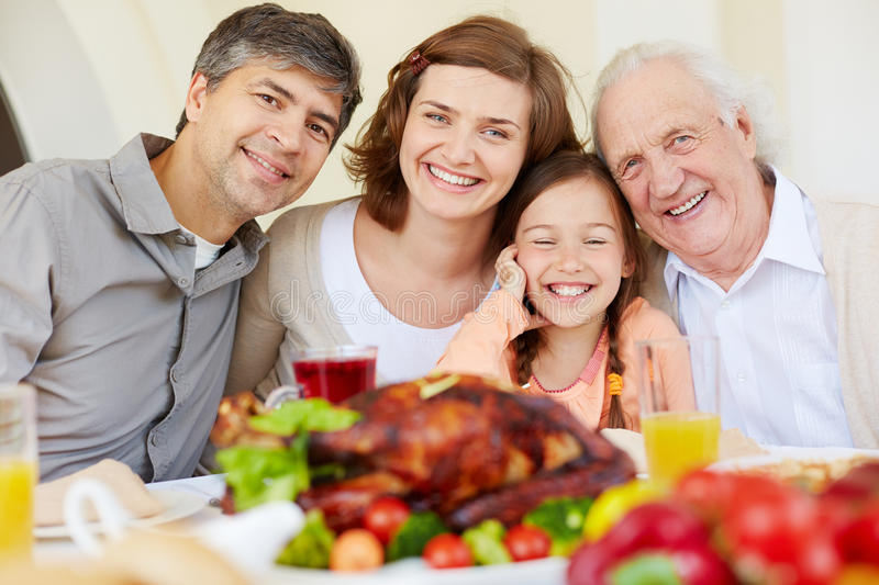 Happy holiday. Portrait of happy family looking at camera by Thanksgiving table royalty free stock image