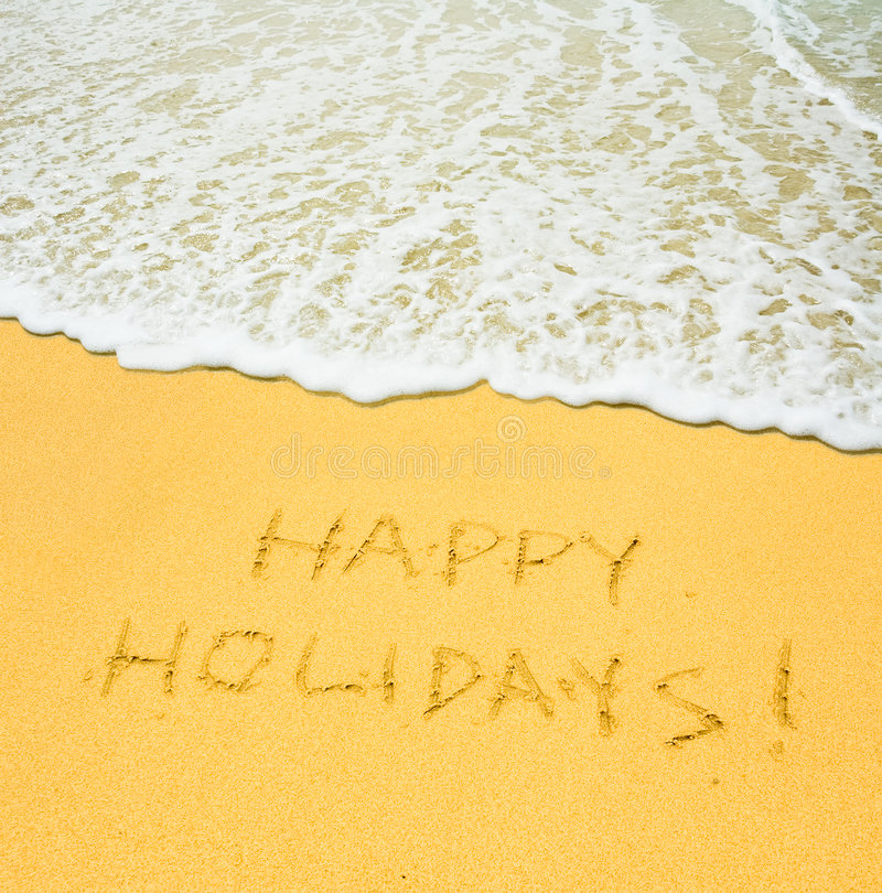 Happy holidays. Written in the sandy beach royalty free stock image