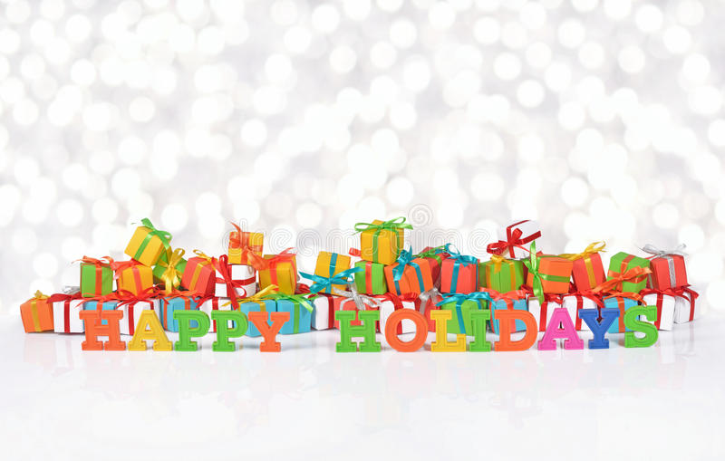 Happy holidays colorful text on the background of gifts. Happy holidays colorful text on the background of varicolored gifts on a bokeh background royalty free stock photo