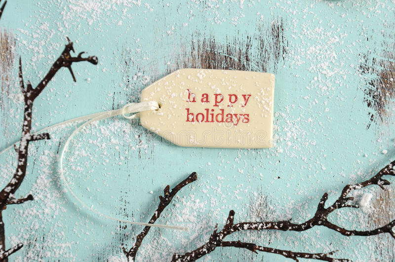 Happy holidays gift tag. Merry Christmas festive baking concept with closeup on happy holidays gift tag on vintage style recycled wood background royalty free stock photo