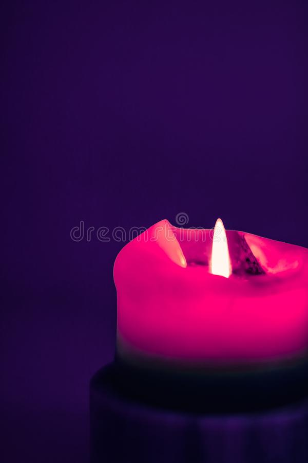 Pink holiday candle on purple background, luxury branding design and decoration for Christmas, New Years Eve and Valentines Day. Happy holidays, greeting card royalty free stock photo