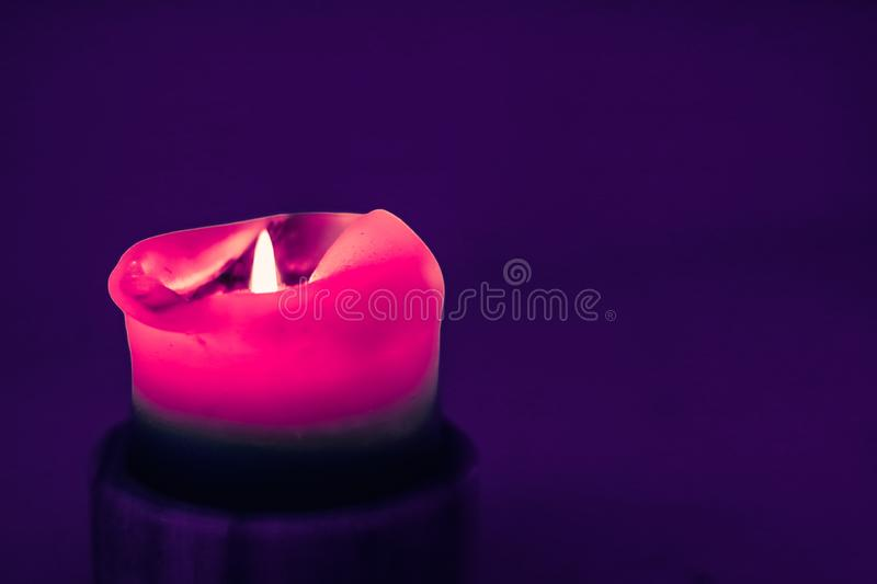 Pink holiday candle on purple background, luxury branding design and decoration for Christmas, New Years Eve and Valentines Day. Happy holidays, greeting card royalty free stock image