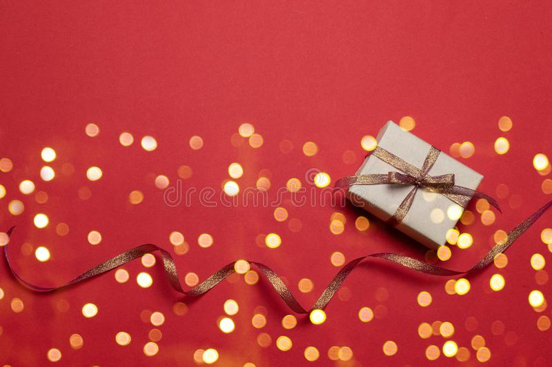 Happy holidays greeting card with star gold glitter sparkle confetti and gift box on red background. Birthday, Valentines day, royalty free stock photography