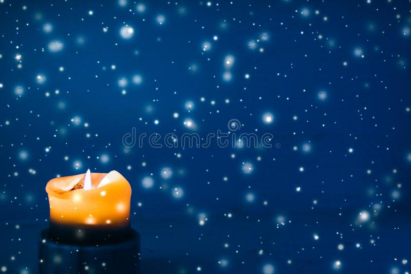 Yellow holiday candle on blue sparkling snowing background, luxury branding design for Christmas, New Years Eve and Valentines Day. Happy holidays, greeting card royalty free stock photography