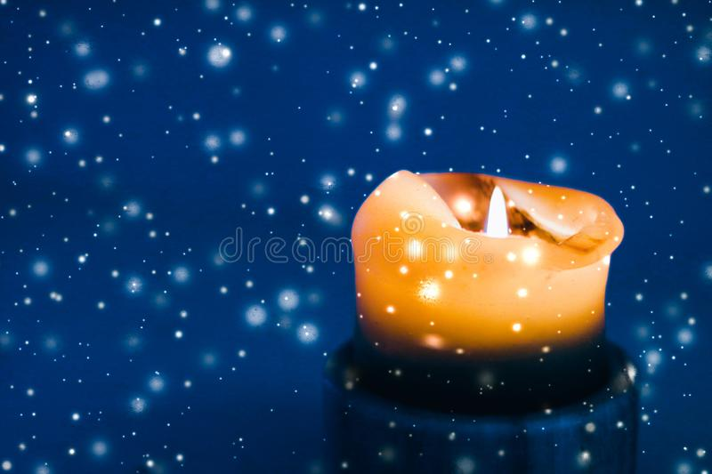 Yellow holiday candle on blue sparkling snowing background, luxury branding design for Christmas, New Years Eve and Valentines Day. Happy holidays, greeting card royalty free stock images
