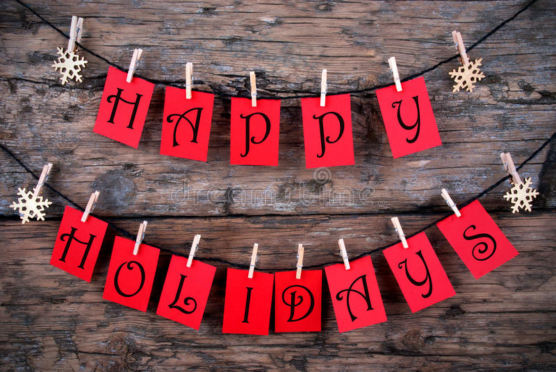 Happy Holidays Greetings on a Line. Happy Holidays Greetings on red Tags Hanging on a Line with Snowflakes, Christmas or Winter Background stock image