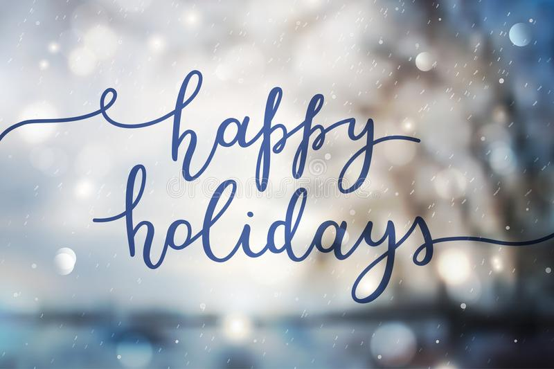 Happy holidays lettering. Happy holidays, lettering on winter blurred background royalty free stock image