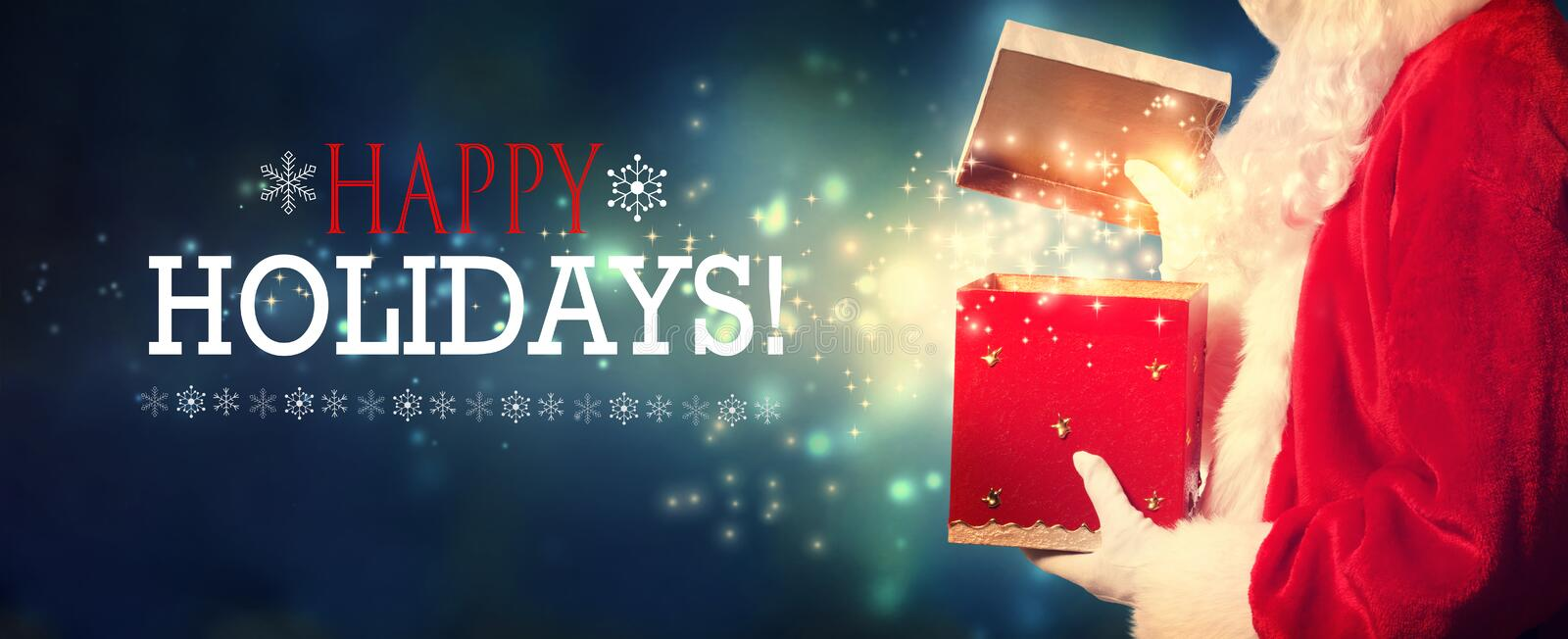 Happy holidays message with Santa opening a gift box stock photos