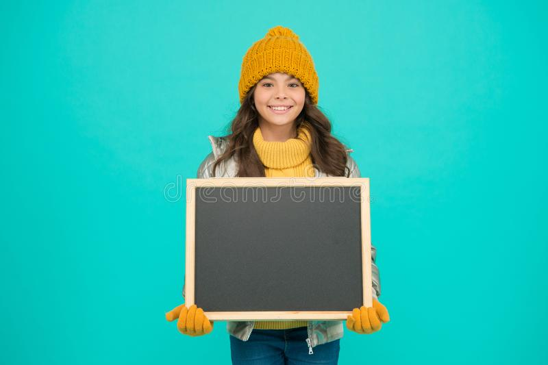 Happy holidays. Show information. Winter entertainment and activities. Presentation concept. Smiling girl wear winter. Outfit blank chalkboard copy space. Fresh royalty free stock photo