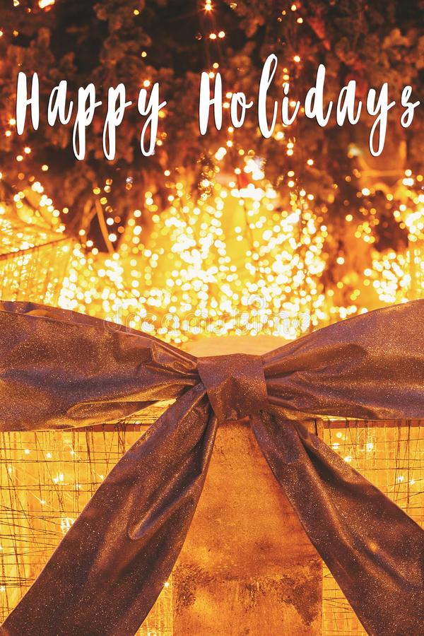 Happy Holidays text on big presents gift boxes with lights under. Christmas tree in evening in illumination lights. Season`s greetings card. Merry Christmas and royalty free stock images