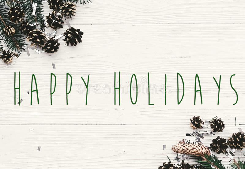Happy Holidays text on modern christmas flat lay with green fir. Branches, golden pine cones and stars. Season`s greetings card. Merry Christmas and Happy new stock photos