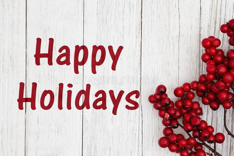 Happy holidays text with red berry branch stock image