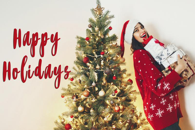 happy holidays text, seasons greetings, merry christmas and happy new year concept. happy stylish woman in santa hat holding many royalty free stock photo