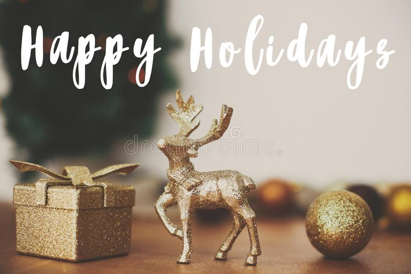 Happy Holidays text sign on golden reindeer, gift box and glitter bauble toys on background of christmas tree with lights on. Rustic background.Season`s royalty free stock photo
