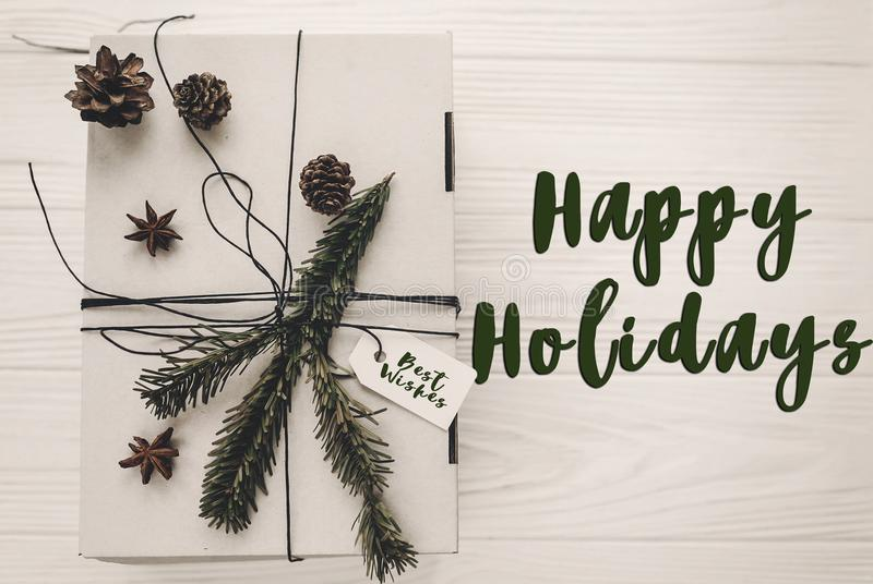 happy holidays text sign, greeting card. stylish christmas rustic gift box flat lay. white present with green tree fir branch and royalty free stock images