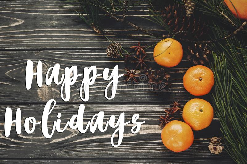 Happy holidays text sign, greeting card. tangerines with green f royalty free stock photo