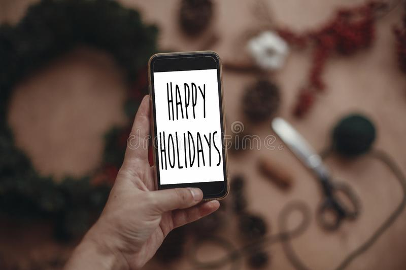 Happy Holidays text sign on phone screen in hand on background of rustic christmas wreath, fir branches,red berries, pine cones. Seasonal greeting card royalty free stock photos
