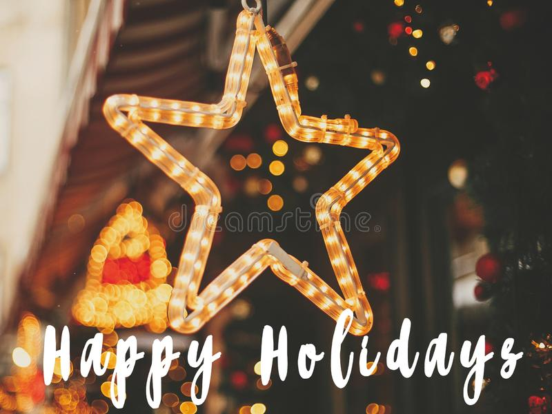 Happy Holidays  text sign on stylish christmas golden star illumination and fir branches with red and gold baubles, golden lights. Bokeh. Seasons greeting card stock photography