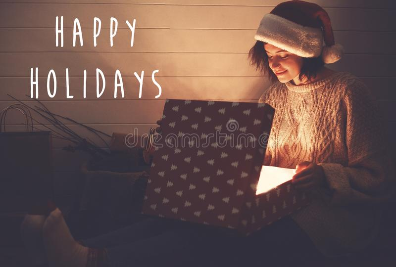 Happy Holidays text sign on stylish happy girl in santa hat opening christmas gift box with magic light in dark room. Merry royalty free stock photo