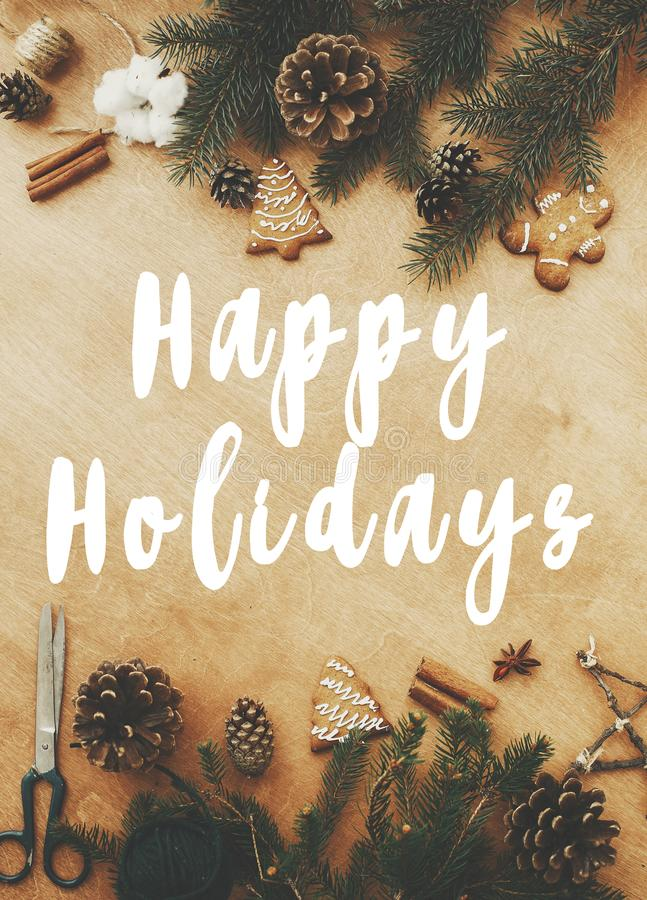 Happy Holidays text sign on stylish rustic frame of pine branches, cones, gingerbread cookies,thread, cinnamon, anise on rural. Wooden table. Season`s greeting stock photos