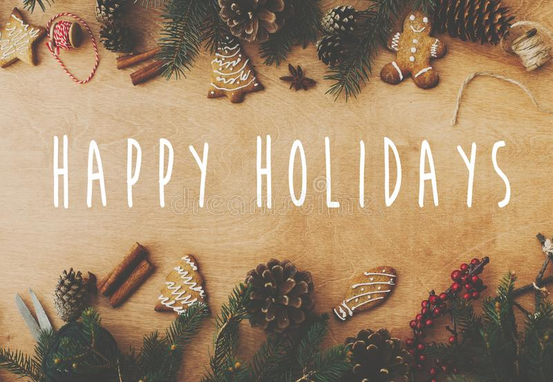 Happy Holidays text sign on stylish rustic frame of pine branches, cones, gingerbread cookies,thread, cinnamon, anise on rural. Wooden table. Season`s greeting stock photo