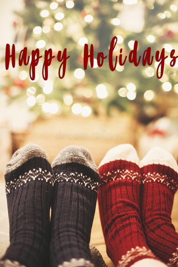 Happy Holidays text on stylish festive socks on couple legs at g royalty free stock photo