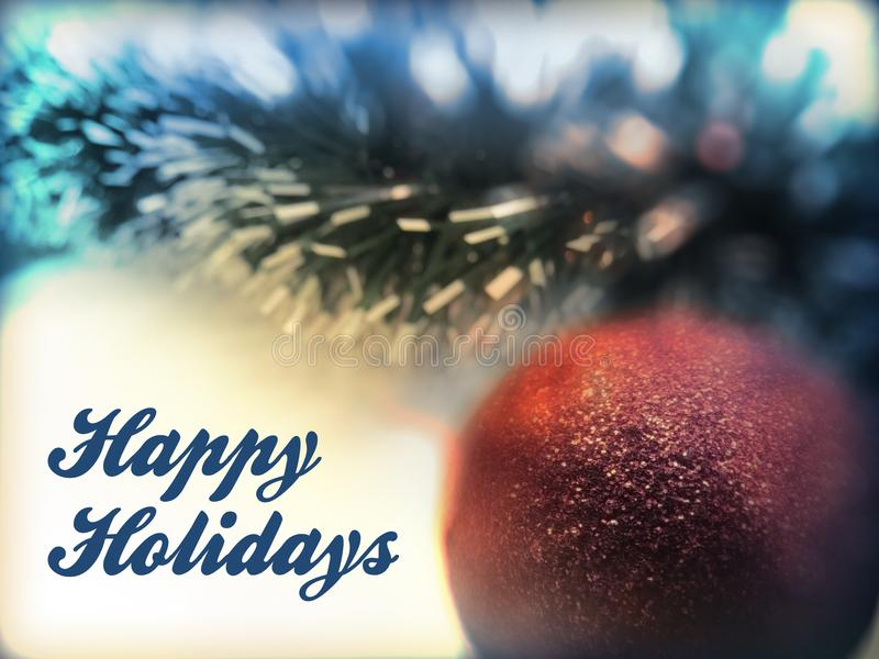 Happy Holidays text in white color on christmas tree ball and star toys and garlands background. stock photography
