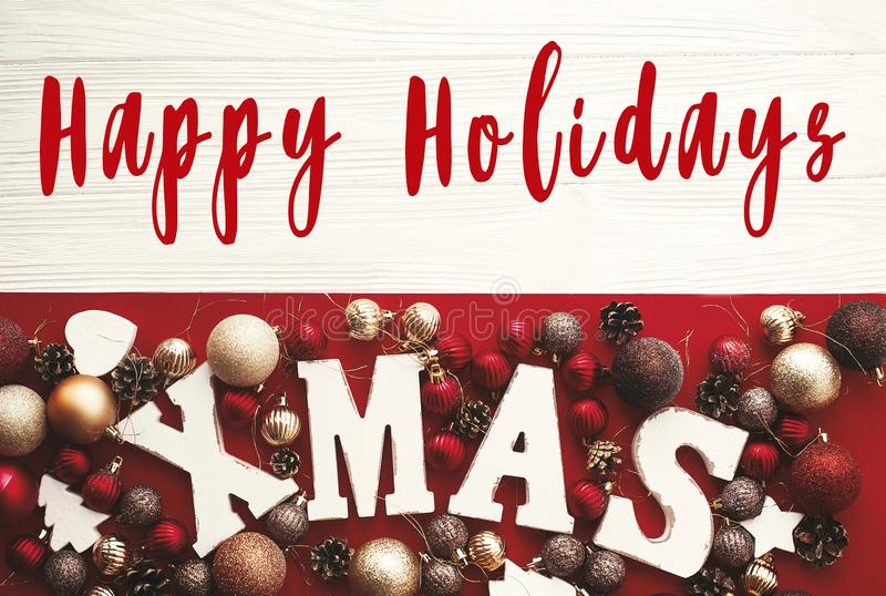 Happy Holidays text on Xmas wooden word with red baubles and orn. Aments on rustic white background, flat lay. Season`s greetings card. Merry Christmas and Happy royalty free stock images